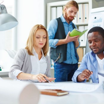 Blond businesswoman pointing at blueprint with her colleagues near by